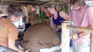Building up the mud oven with clay, sand, corn husk, and water